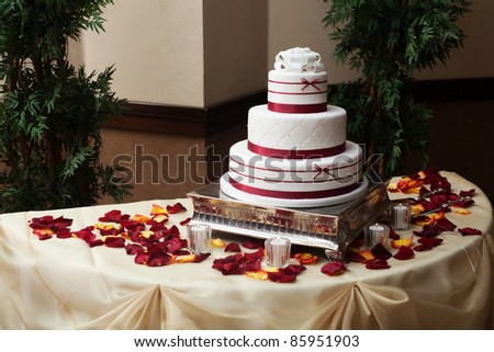 A beautiful wedding cake with red flower petals - stock photo
