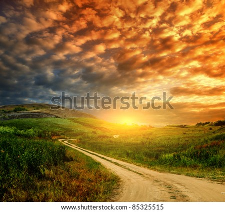 A beautiful winding country road through the hills - stock photo