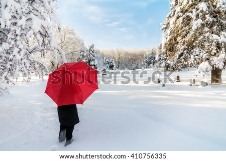 A beautiful winter snow scene with a woman walking in a cemetery with a red umbrella as the snow clings to the trees. - stock photo