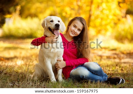 A beautiful woman and her dog (Labrador retriever) posing in autumn park. Red and orange leaves around.