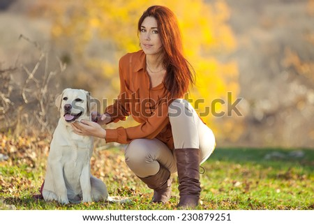 A beautiful woman and his dog (Labrador ) posing outside - stock photo