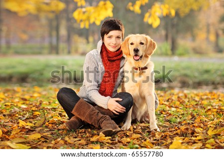 A beautiful woman and his dog (Labrador retriever) posing outside - stock photo