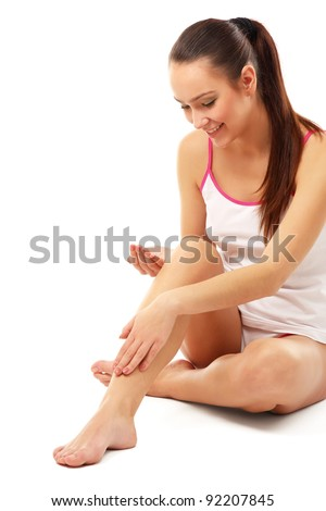 A beautiful woman applying cream on her legs, isolated on white