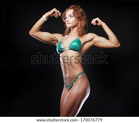 A beautiful woman bodybuilder posing in green  bikini - stock photo