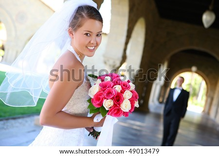 A beautiful woman bride at church during wedding with groom in the background - stock photo