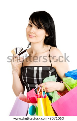 A beautiful woman carrying shopping bags and credit cards - stock photo
