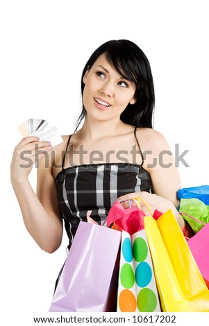 A beautiful woman carrying shopping bags and multiple credit cards - stock photo