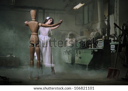 A beautiful woman dances with a wooden dummy - stock photo
