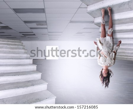 a beautiful woman defying gravity in a large empty warehouse - stock photo