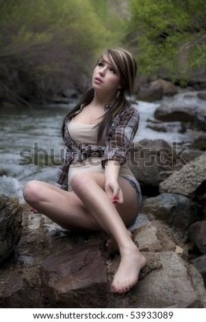 A beautiful woman dressed like a cowgirl on a rock by the river. - stock photo