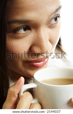 A beautiful woman drinking a hot cup of coffee - stock photo