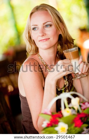 A beautiful woman drinking tea at a restaurant in tropical resort - stock photo