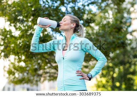 A beautiful woman drinking water on a sunny day - stock photo