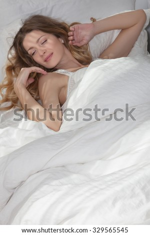 A beautiful woman early in the morning lying on the bed with his back, the sun's rays shine through the window .Beautiful girl sleeping in the early morning in my warm cozy bed
