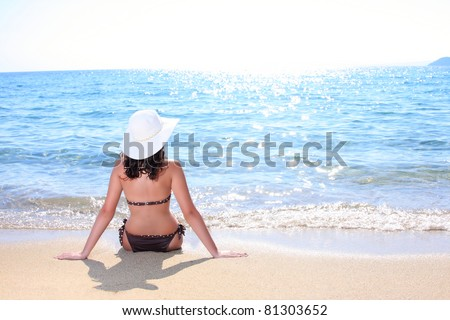 A beautiful woman facing the sea on a vacant beach in paradise - stock photo