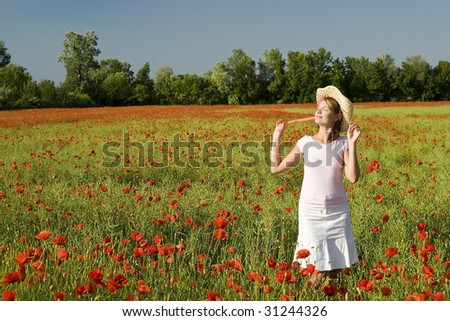A beautiful woman feels happy on the poppy field.