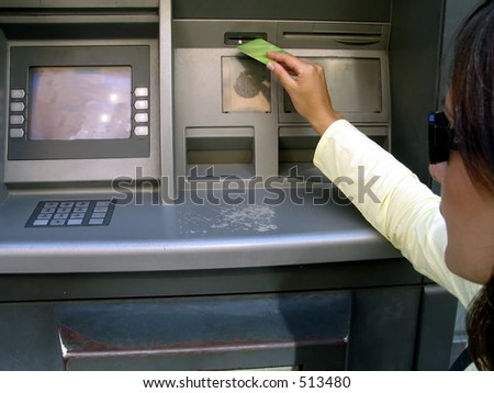 a beautiful woman getting money with her credit card at the ATM, - stock photo