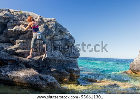 A beautiful woman goes bouldering while rock climbing on the shore line of the Great Lakes.