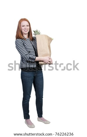 A beautiful woman grocery shopping holding a brown paper bag - stock photo