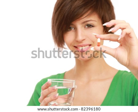 A beautiful woman holding a pill and water, isolated on white - stock photo