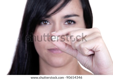 A beautiful woman holding a pill, focus on pill - stock photo