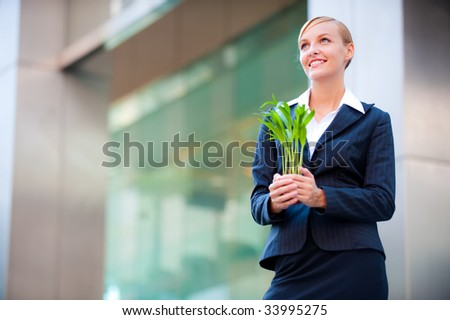A beautiful woman holding a plant to signify business growth