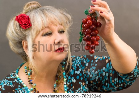 A beautiful woman holds a red grape - stock photo