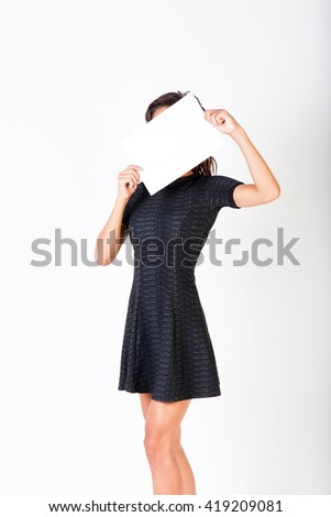 A beautiful woman holds out a blank paper and hiding her face isolated on white background - stock photo