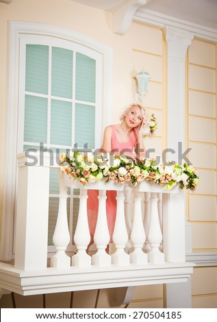 A beautiful woman in a dress. The picture on the balcony - stock photo