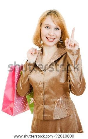 A beautiful woman in a gold suit with shopping points a finger upward on a white background.