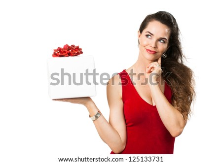 A beautiful woman in a red dress holding a beautifully wrapped gift and thinking and looking at copyspace. Isolated on white.