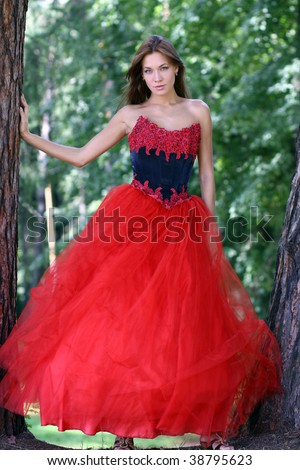 A beautiful woman in a red dress standing among trees in park