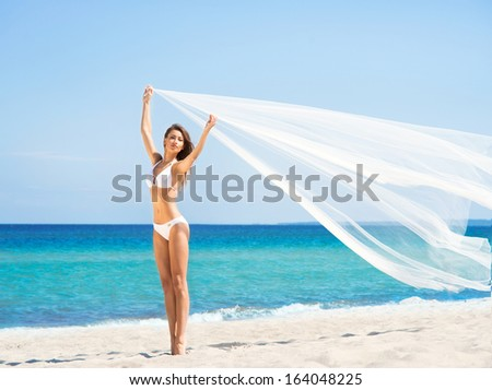 A beautiful woman in a swimsuit posing with a silk blanket on the beach - stock photo