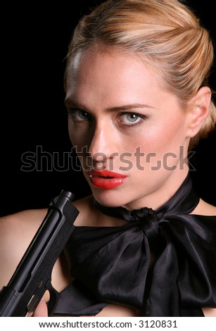 a beautiful woman in evening dress with a pistol pointing at her - stock photo