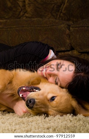A beautiful woman in her early 40s spending time with a very handsome Golden Retriever Dog at home. - stock photo