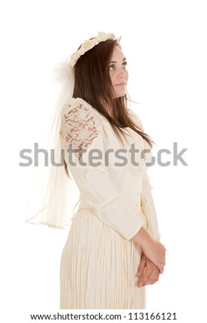 A beautiful woman in her vintage wedding dress looking  away from the camera - stock photo