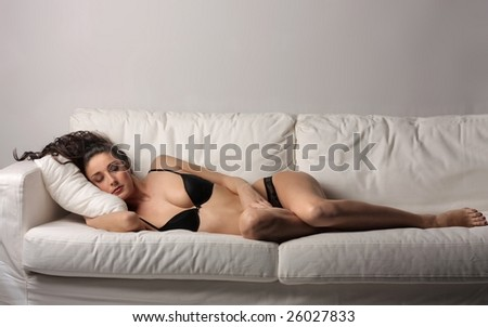 a beautiful woman in lingerie relaxing on a sofa - stock photo