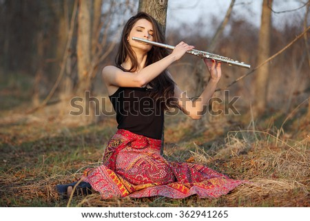 A beautiful woman in red skirt posing in a forest while playing on a flute. - stock photo