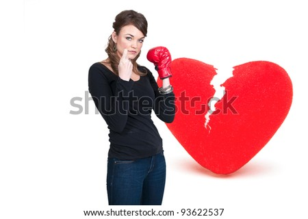 A beautiful woman in wearing a boxing glove in front of a broken heart - heartbreaker - stock photo