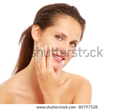 A beautiful woman is applying cream on her face over white - stock photo