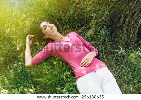 A beautiful woman is laying on her back in the grass, with her eyes closed. She is relaxing, enjoying the shadow of the tree in a sunny day. - stock photo
