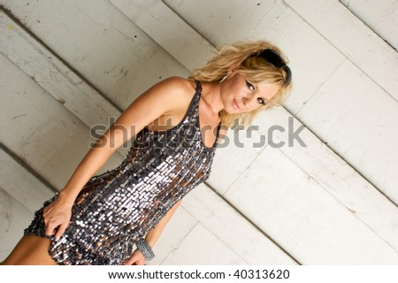 A beautiful woman is looking sexily at the viewer in a silver sequined dress as she pulls up the hem. - stock photo