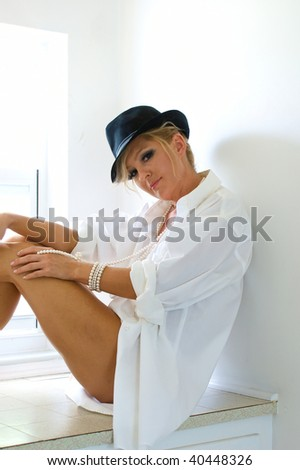 A beautiful woman is sitting on a window seat wearing only a man's hat and dress shirt, looking at viewer. - stock photo