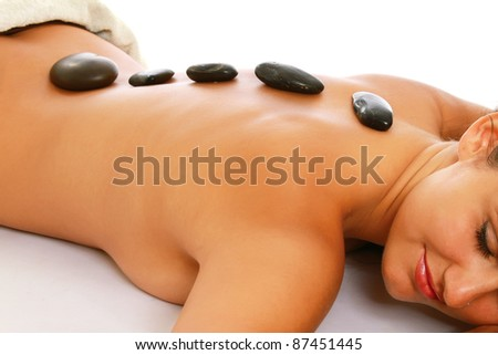 A beautiful woman lying during a stone therapy isolated on white - stock photo
