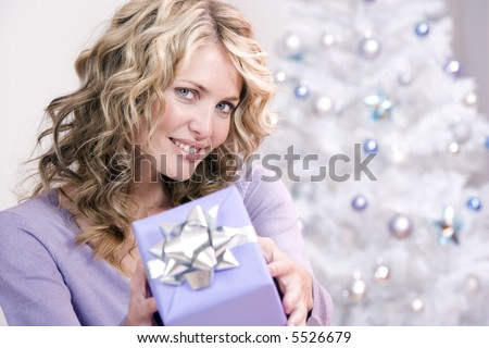 A beautiful woman offering a christmas gift - stock photo