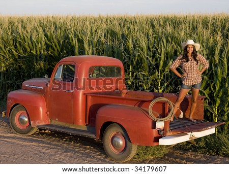 A beautiful woman on the farm with her old pickup truck - stock photo