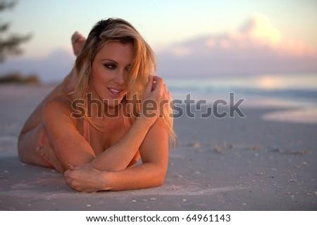 A beautiful woman posing in a bikini at the beach at sunset. - stock photo