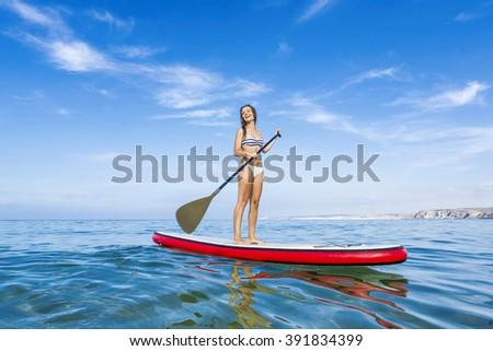 A beautiful woman practicing paddle on a beautiful sunny day - stock photo