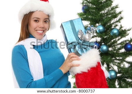 A beautiful woman putting a present into a stocking at Christmas