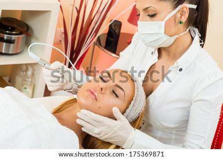 a beautiful woman receiving a facial treatment - stock photo